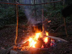billy-can heating water over the campfire to boil and purify